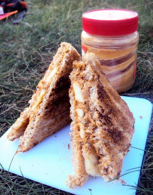 KANAPKA ELVISA PRESLEYA  Potrzebujesz: 2 kromki tostowego chleba, masło orzechowe, kilka plasterków banana  Przygotowanie: kromki chleba smarujemy obficie masłem orzechowym po jednej stronie. Układamy plasterki banana. Składamy  kromki masłem orzechowym do siebie. Pieczemy na grillu, takim już niezbyt mocno się żarzącym, po obu stronach, tak by chleb lekko zbrązowiał, a nadzienie było ciepłe. Łatwe i zdrowe.  fot. jajem.blogspot,com